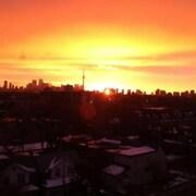 Vue sur un lever de soleil orangé à Toronto.