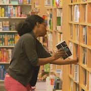 Une femme range des livres dans un rayon d'une librairie