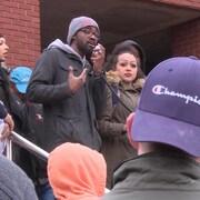Le conseiller municipal Lindell Smith tient un micro alors qu'il s'adresse aux manifestants sur les marches du quartier général de la police d'Halifax le 30 mars 2019.