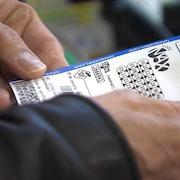 Un homme tient entre ses mains un billet de loterie Lotto Max.