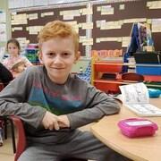 Un enfant de deuxième année dans sa classe regardant la caméra.