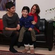 Deux femmes et un jeune garçon sont assis sur un sofa.