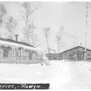 Des bâtiments en bois rond aux débuts de Rouyn-Noranda, en hiver.