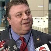 Le conseiller municipal Magliocca est entouré des micros de journalistes lors d'une entrevue.