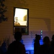 Une femme à la fenêtre se fait un masque devant un public posté à l'extérieur de la maison.