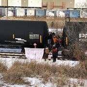Des manifestants entre des wagons sur une voie ferrée.