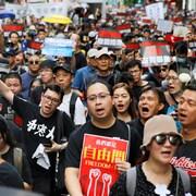 Des gens tiennent des pancartes au cours d'une manifestation.