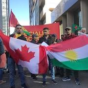 Des hommes présentent les drapeaux canadien et kurde.