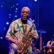 Manu Dibango est sur scène et tient un saxophone dans les mains.