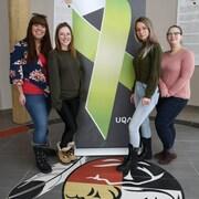 Quatre jeunes femmes posent de chaque côté d'une affiche avec un ruban vert symbolisant la persévérance scolaire.