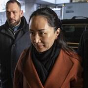 Meng Wanzhou se dirigeant vers l'entrée de l'édifice de la Cour, regardant droit devant elle.