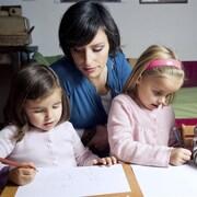 Une mère fait l'école à la maison à ses enfants.