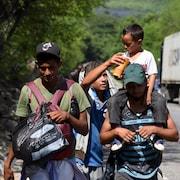 Des migrants marchent sur la route.
