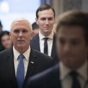 Un homme aux cheveux blancs et portant un complet avec une cravate marche dans un corridor, suivi et précédé de deux autres hommes.
