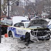 La scène d'un violent accident impliquant une voiture de la police de Montréal, dont l'avant est entièrement détruit.