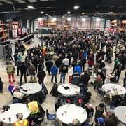 Environ une centaine de personnes sont rassemblées dans un grand local.