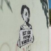 Une murale à Port-au-Prince montrant une petite fille tenant une affiche faisant référence au scandale PetroCaribe en Haïti.