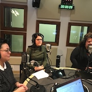 Nancy Bouchard, Kathy Allen et Lee Faubert parlent au micro dans le studio de radio.
