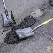 Deux pelles qui aplatissent l'asphalte.