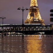 Les rives inondées de la Seine, en soirée, à Paris avec la tour Eiffel et un train passant au loin.