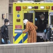 Un patient descend d'une ambulance avant d'entrer à l'hôpital.