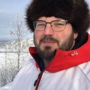 Paul Robitaille, responsable évènementiel et du marketing à l'Association des visiteurs du Klondike, regarde l'objectif devant une grande plaine de neige.