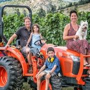 une famille de trois enfants sur un tracteur, la femme a un chien sur les genous, avec la vigne en fond.