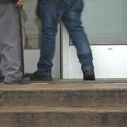 Les jambes de deux hommes âgés devant une porte.