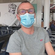 Un homme portant un masque assis dans une aire de repos d'un aéroport.