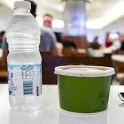 Une bouteille d'eau, un contenant et une cuillère en plastique sur une table.