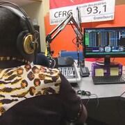 Un animateur radio de dos, devant sa console, à CFRG Gravelbourg.