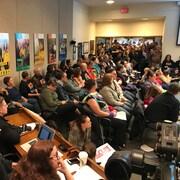 Des dizaines de personnes massées dans une salle écoutent attentivement des débats qui semblent se dérouler hors cadre.