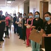 Dans un couloir, des employés, masqués, tiennent  les repas livrés par les Enfants terribles.