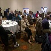 Une vingtaine de personnes sont assises autour de plusieurs tables en train d'écouter un discours lors de la réunion du Réseau santé en français de la Saskatchewan.