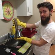 Jordan Robinson tient une pipe à eau au-dessus de son évier.