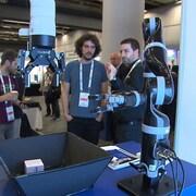 Deux hommes observent des bras robotiques manipuler des objets sur une table.