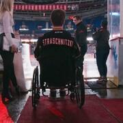 Ryan Straschnitzki en chaise roulante à l'entrée d'une patinoire.