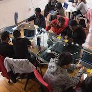 Des jeunes et des employés d'Osedea sont assis autour de tables et travaillent sur des ordinateurs.