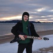 Samuel Chiasson avec sa guitare au bord de l'eau en hiver.