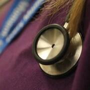 Un stéthoscope sur la poitrine d'une femme qui porte un uniforme violet.