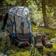 Des bottines et un sac à dos de randonneur dans une clairière en pleine forêt.
