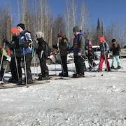 Un groupe d'élèves debout sur un terrain enneigé plat. Ils portent des ski raquettes et tiennent des bâtons de ski.