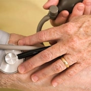 La main du médecin avec son appareil et le bras de la patiente.