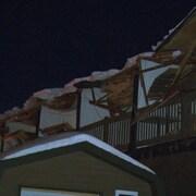 Vue sur le toit d'un bâtiment effondré sous la glace et la neige en pleine nuit.
