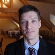 Un jeune homme aux yeux bleus avec une cravate.