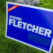 Une affiche plantée dans une pelouse où est écrit en anglais Élisez à nouveau Steven Fletcher. Dans le bas à droite un logo du Parti conservateur a été caché à la peinture bleu, mais on peut encore le voir un peu.