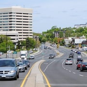 Une rue du centre-ville de Sudbury. Les voitures sont en mouvement. Au loin, le château d'eau de Sudbury.