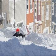 Une personne est occupée à pelleter après le passage du blizzard, à Terre-Neuve.