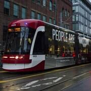 Des femmes courent pour ne pas manquer leur tramway.