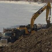 Un camion et une pelle mécanique sur les berges d'une rivière.